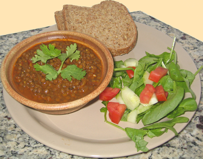 Cooked Masoor/Red Lentil soup, served with bread and salad